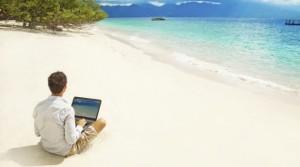 Hombre-con-un-portátil-en-la-playa-mirando-al-mar-619x346